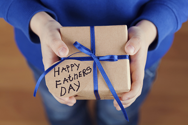 Childrens hands holding gift, present with tag Happy fathers day
